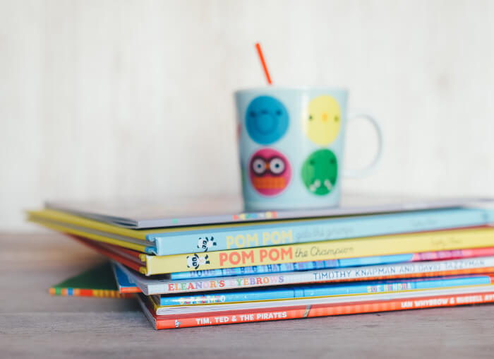 a pile of kids books with a kid mug on top