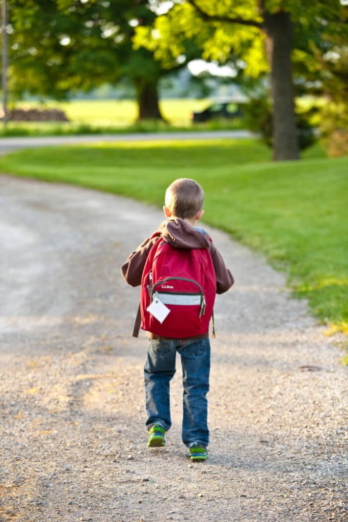 Boy walking away with a red backpack
