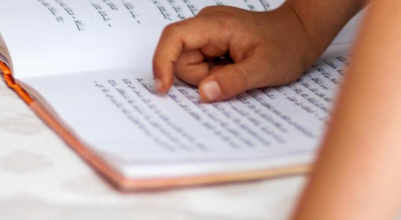 kids hands on a book