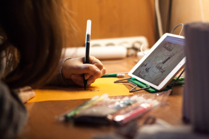 child with long hair drawing while looking at a tablet with hearphones on