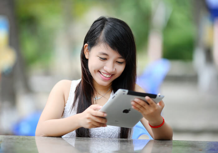 student girl looking at her ipad outside
