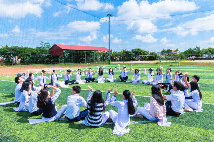 group of student sitting on a football field in circle with their hands raised