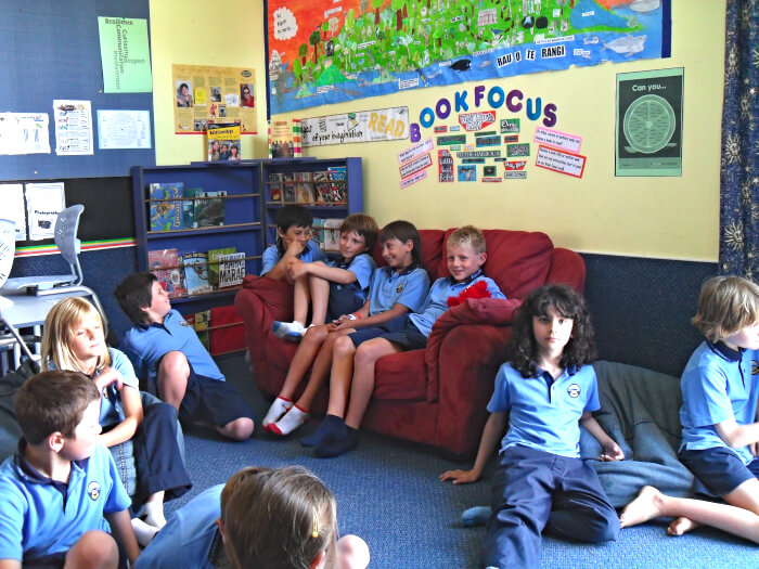 Group of kids seating on the floor and on a sofa in class
