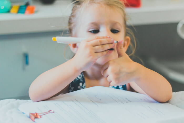 girl with a pen looking at her colored finger