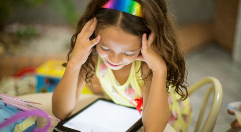 young girl student looking over her tablet smiling