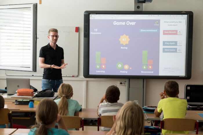 teacher in front of his classroom working with a classroom interactive tool