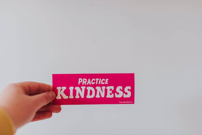 hand holding a paper with the words practice kindness