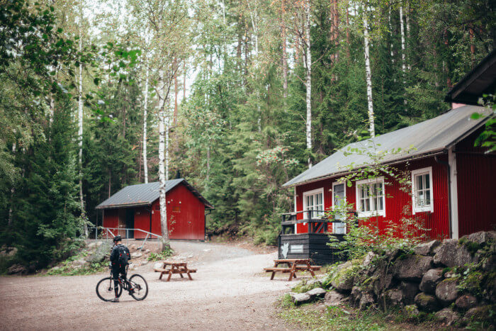 red cabins in the woods with a man standing next to his mountain bike