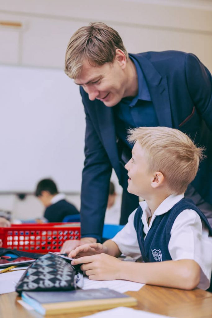 male teacher standing talking to a seated student