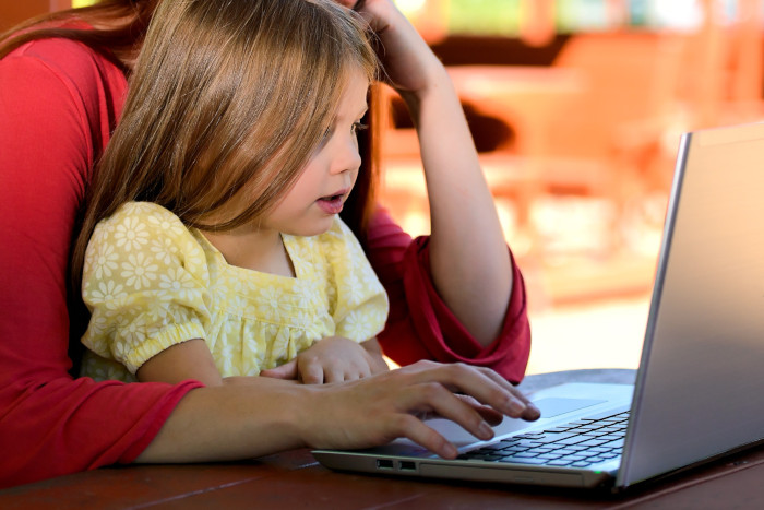 Little girl on the computer with an adult