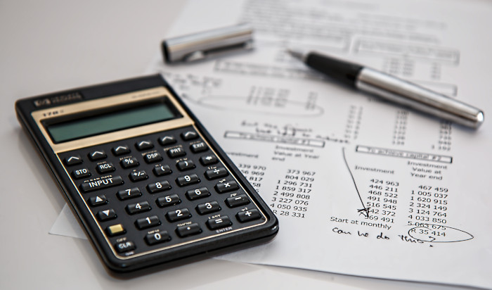 calculator with paper with budget calculations on it