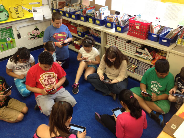 group of students seated on the floor looking at their devices
