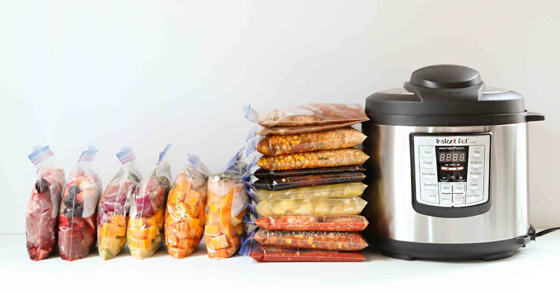Instant pot shown with freezer bags full of prepared food, cooked ahead and frozen using the Once a Month meal plan.