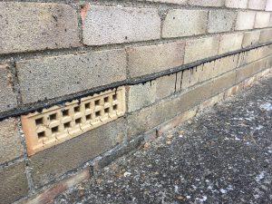 Line of bitumen damp proof membrane and a ventilation air brick