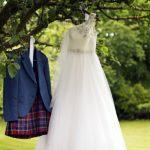 Kilt and wedding dress hanging on a tree