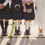 Groom and groomsmen wearing scottish traditional kilt and bride in white dress