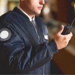 Man in Uniform communicating through handheld walkie talkie