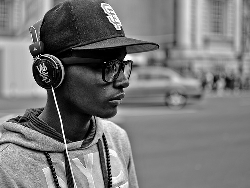 Young Man Listening to Music on Headphones in the Streets