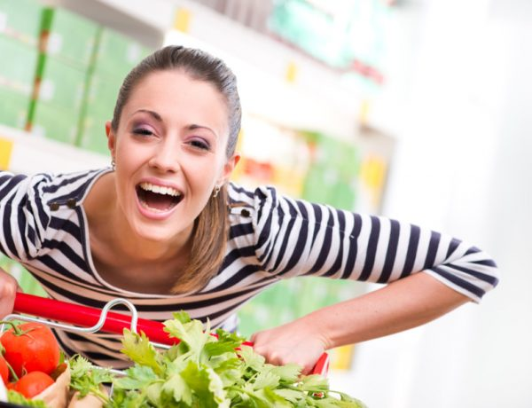 This image of a happy woman buying vegetables to embrace clean eating is goofy... and gendered.