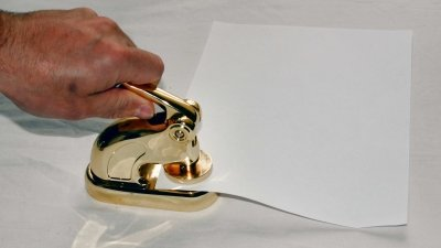 Blinddrukstempel, droogstempel, preegstempel, reliëfstempel, diepdrukstempel of blinddruktang om afdruk in reliëf op papier te zetten.