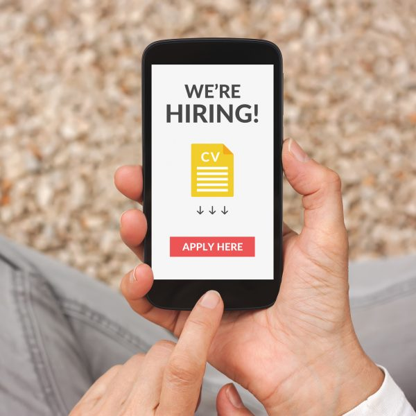 Hands holding smartphone with we are hiring apply now concept on screen. All screen content is designed by me