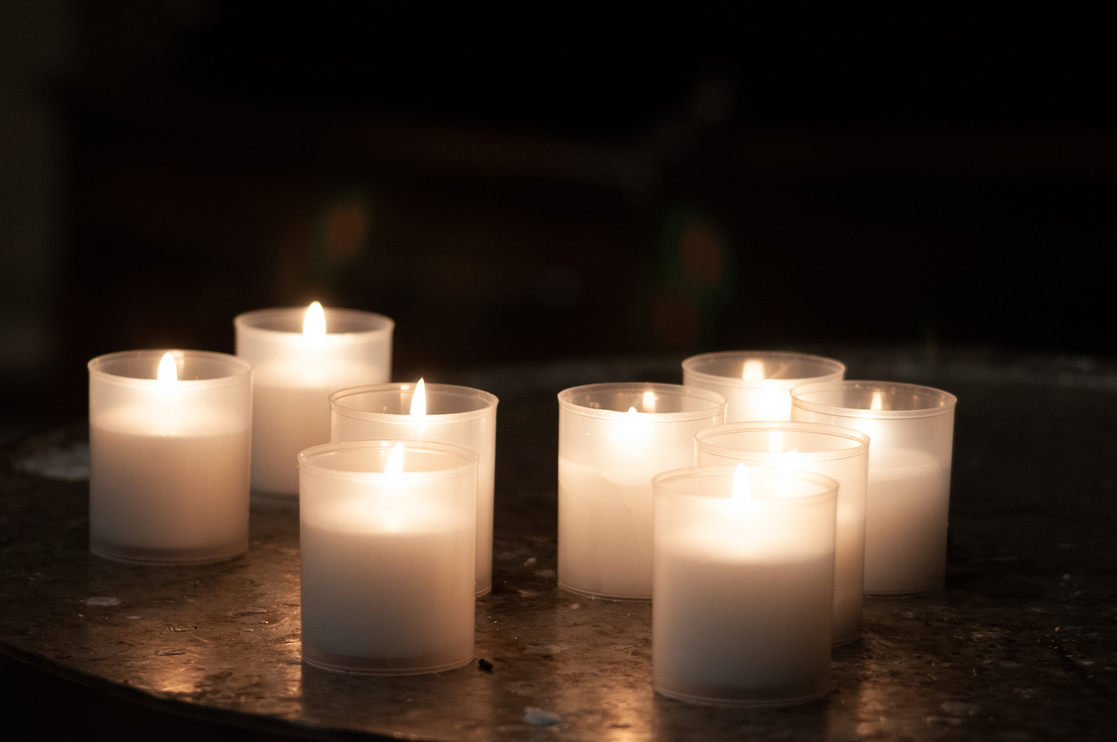 several lit candles in a dark room