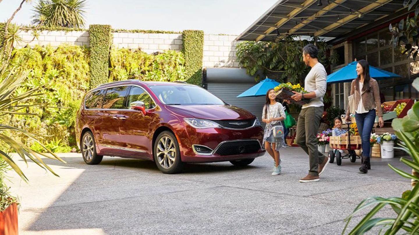 family walking past a red 2019 chrysler pacifica