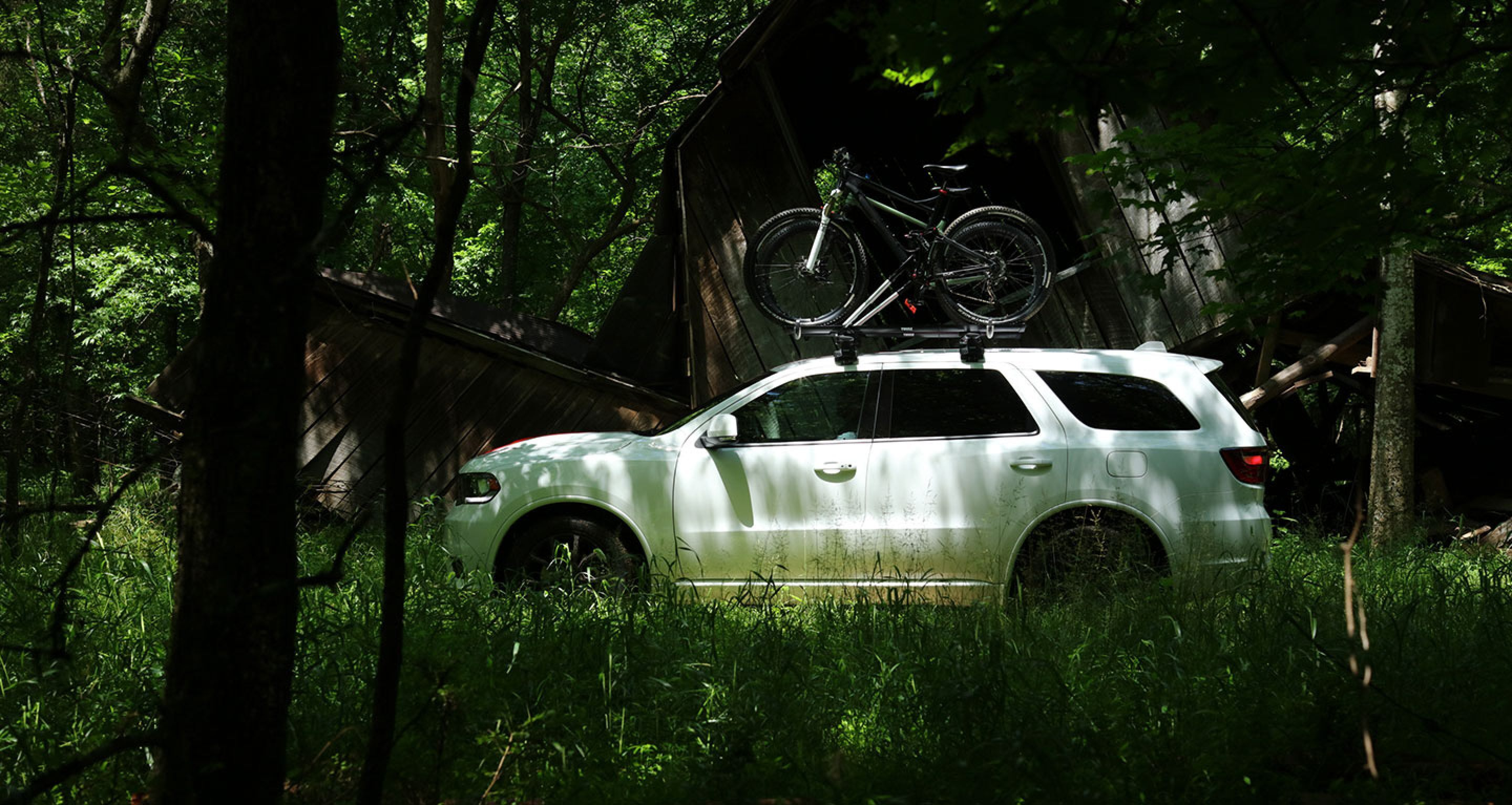 white 2019 dodge durango parked in the woods with a bike on top