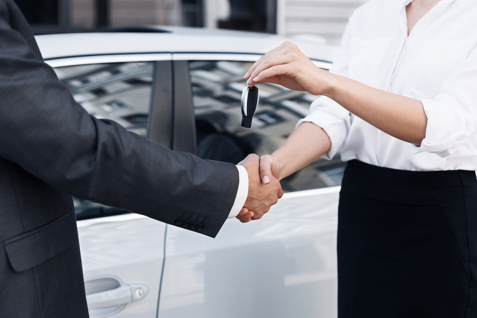 man and woman shaking hands and woman is handing man keys to a new vehicle