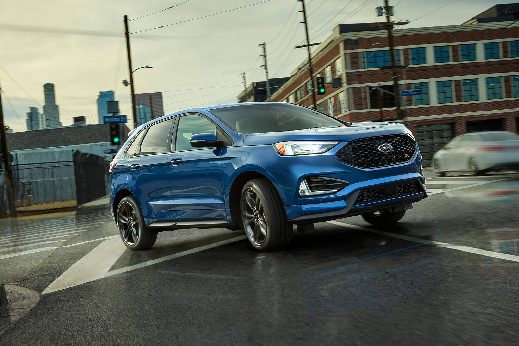blue 2019 ford edge st driving on a wet road in the city