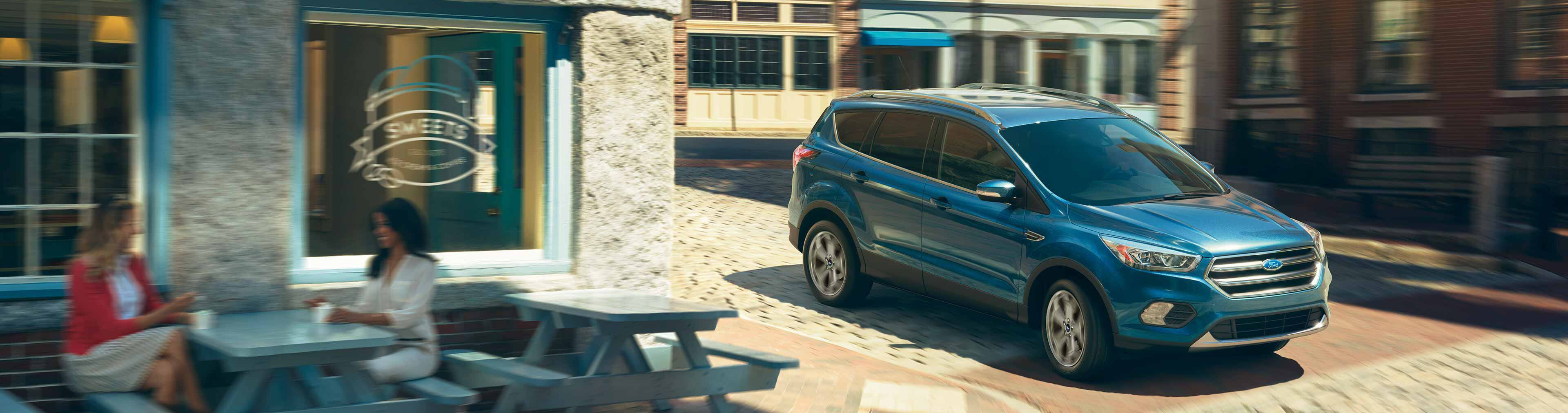blue 2019 ford escape driving past an ice cream shop