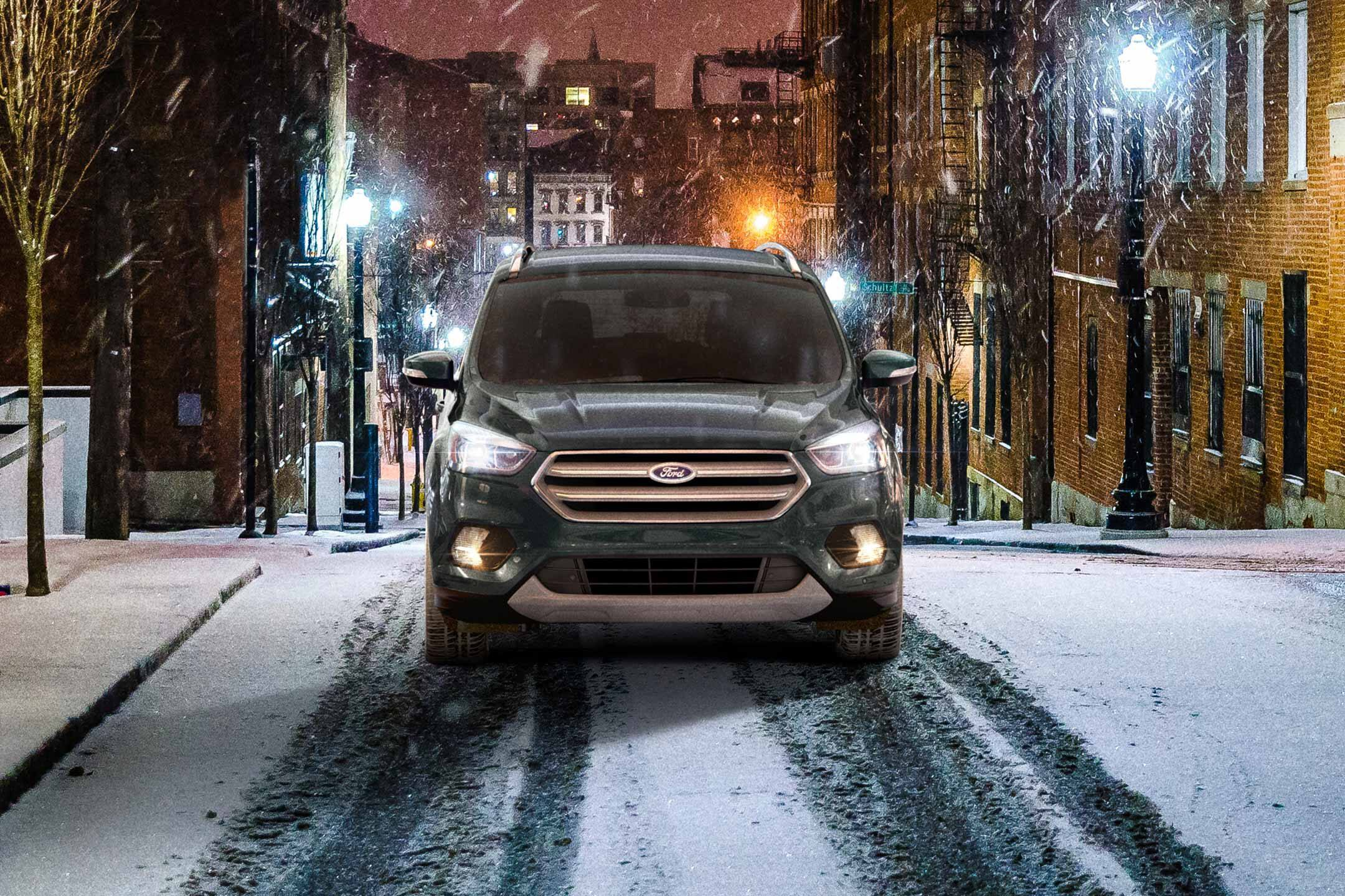 green 2019 ford escape driving on snowy streets in the city