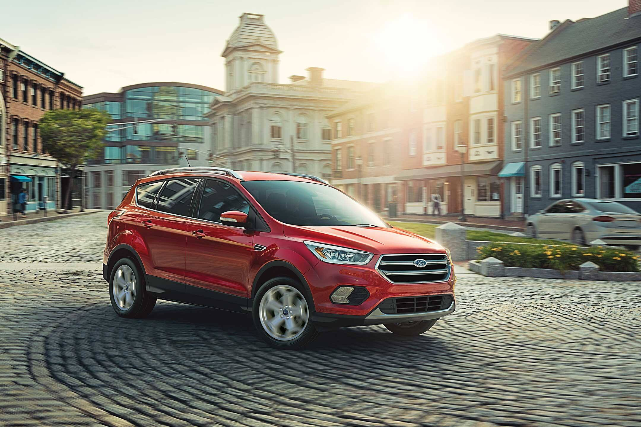 red 2019 ford escape driving through the city
