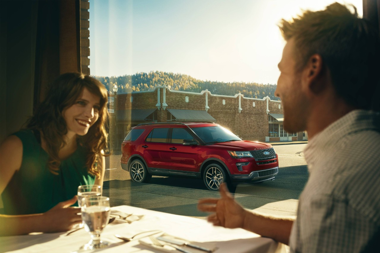 Couple at restaurant while red 2019 Ford Explorer is parked outside