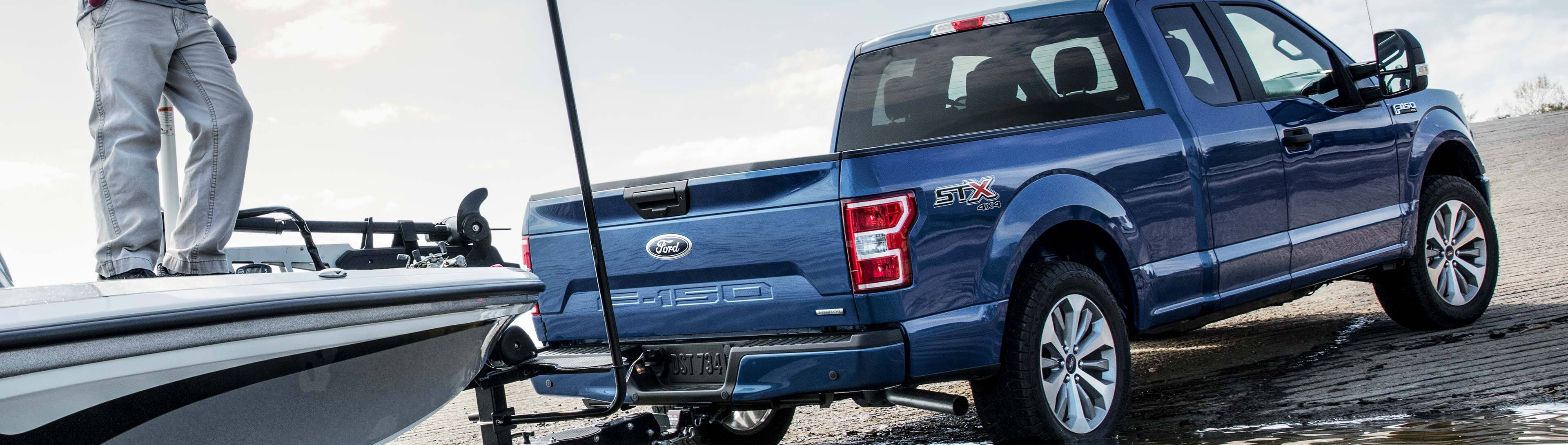 blue 2019 ford f-150 stx 4x4 towing a boat