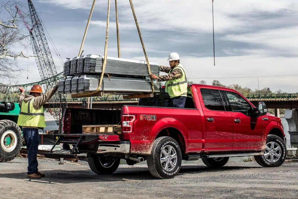 Workers loading up a red 2019 Ford F-150