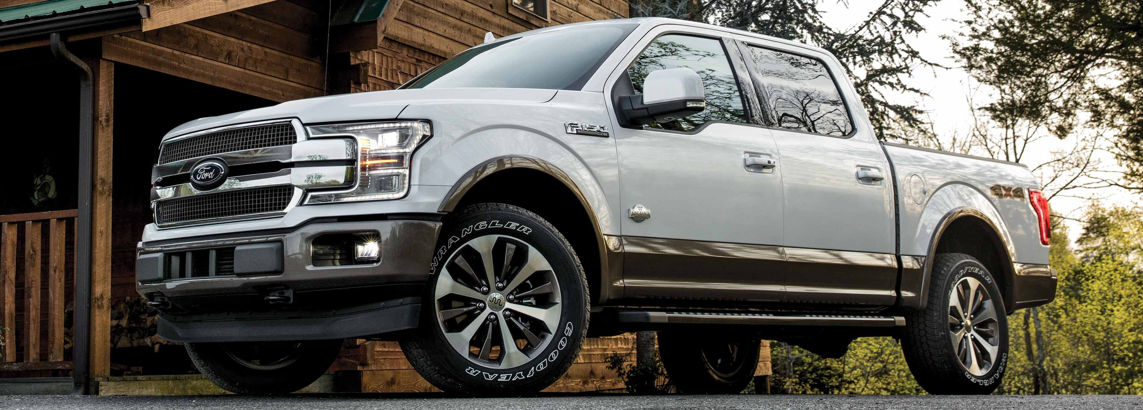 white 2019 ford f-150 parked in front of a cabin