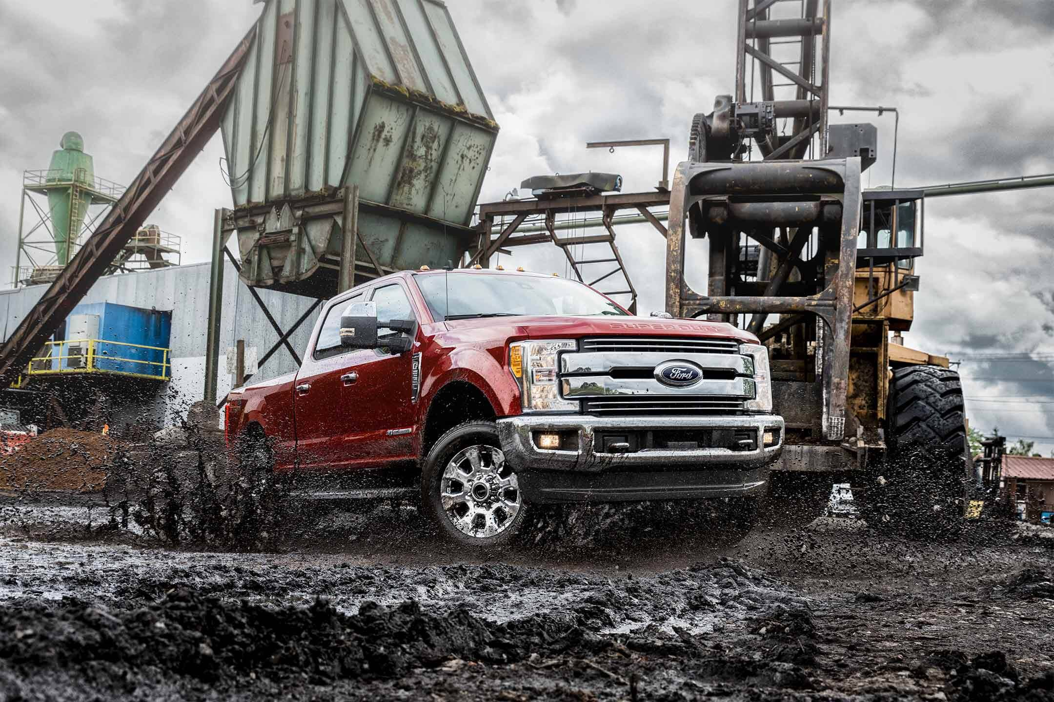 red 2019 ford f-250 super duty driving through mud in a construction site