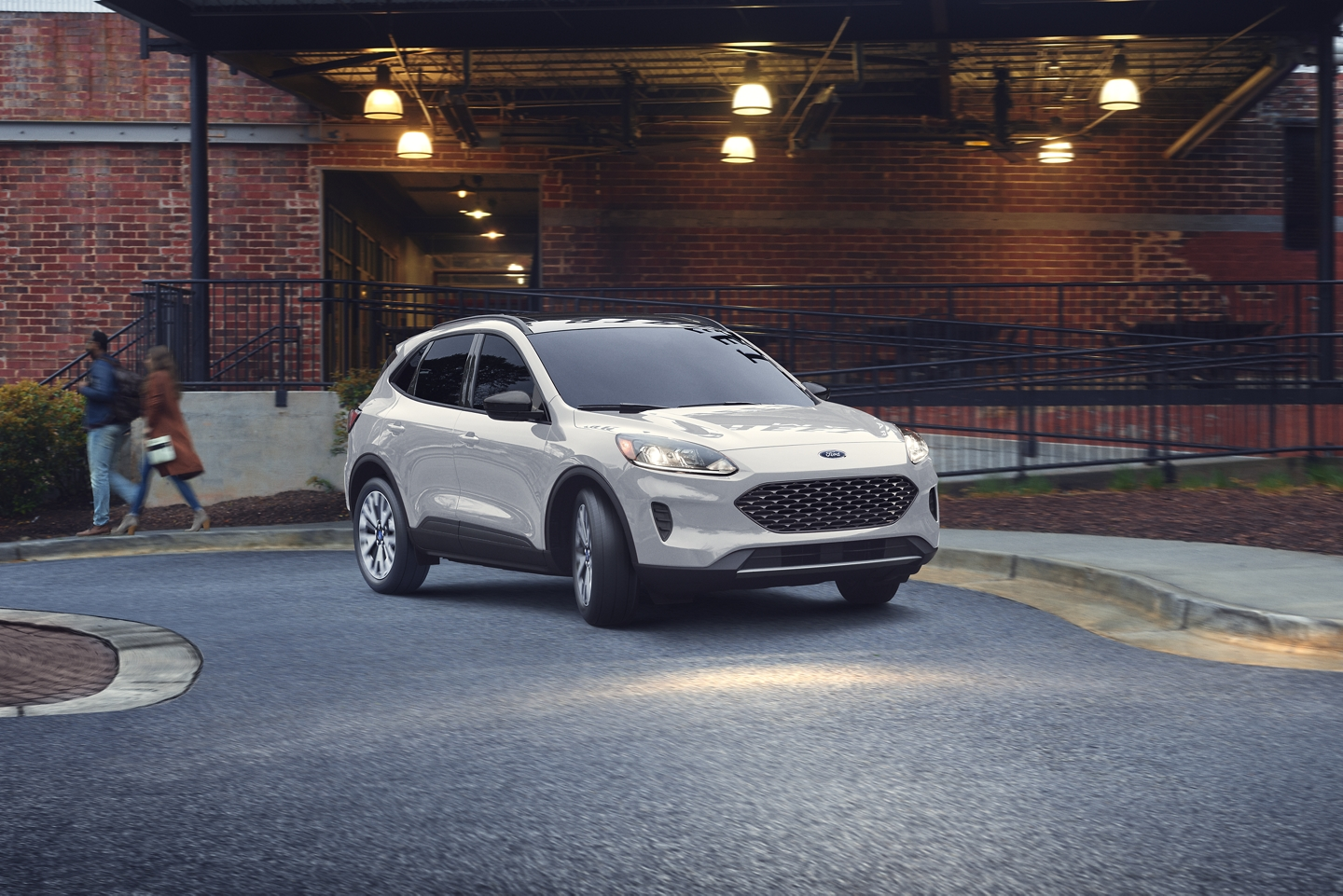 white 2020 ford escape driving past brick building