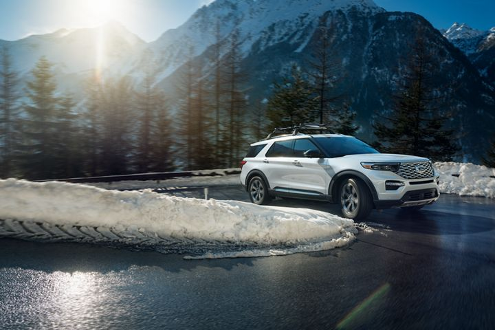 white 2020 ford explorer driving up a road on a snowy mountain