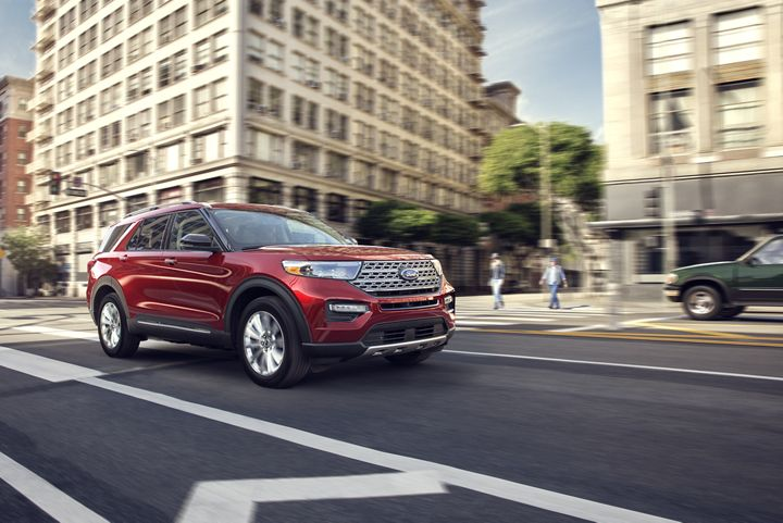red 2020 ford explorer driving through the city
