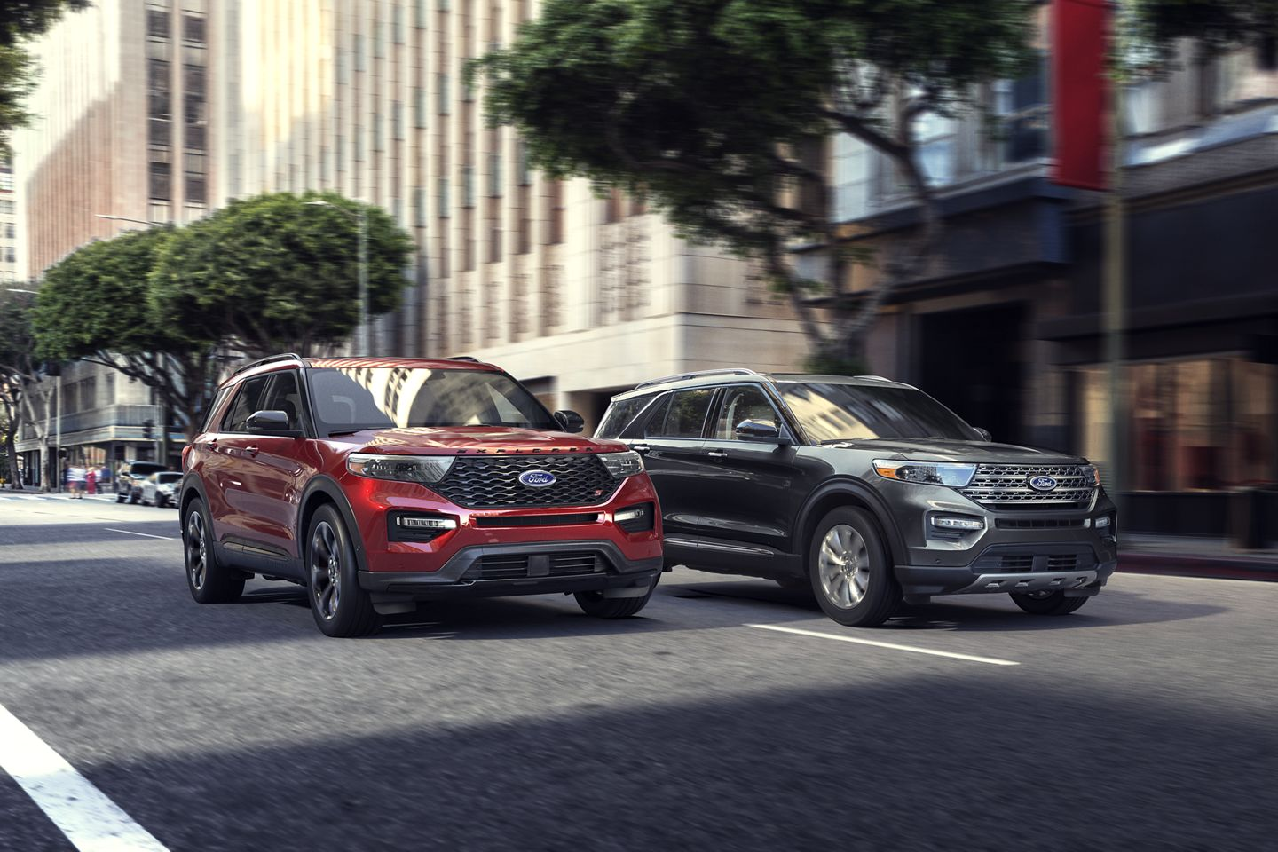 two 2020 ford explorers driving in the city