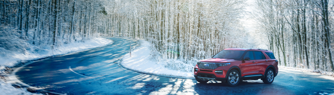 red 2020 ford explorer driving on winding road in snowy woods