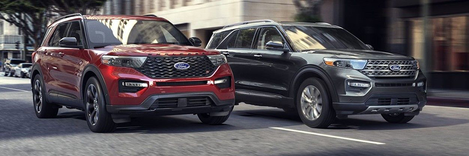 a red and a grey 2020 ford explorer driving down the street