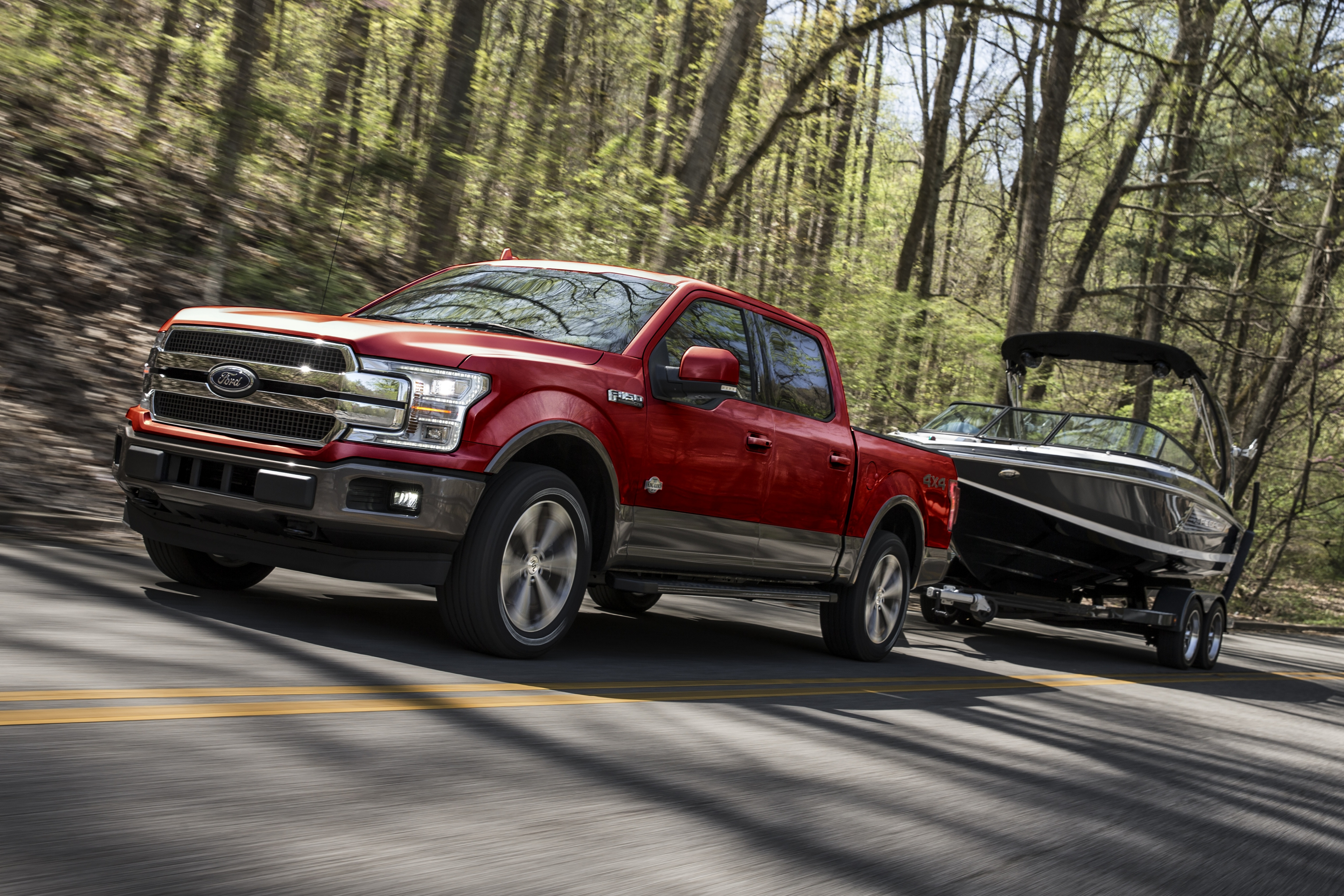 red 2020 ford f-150 towing a boat on a road in the woods
