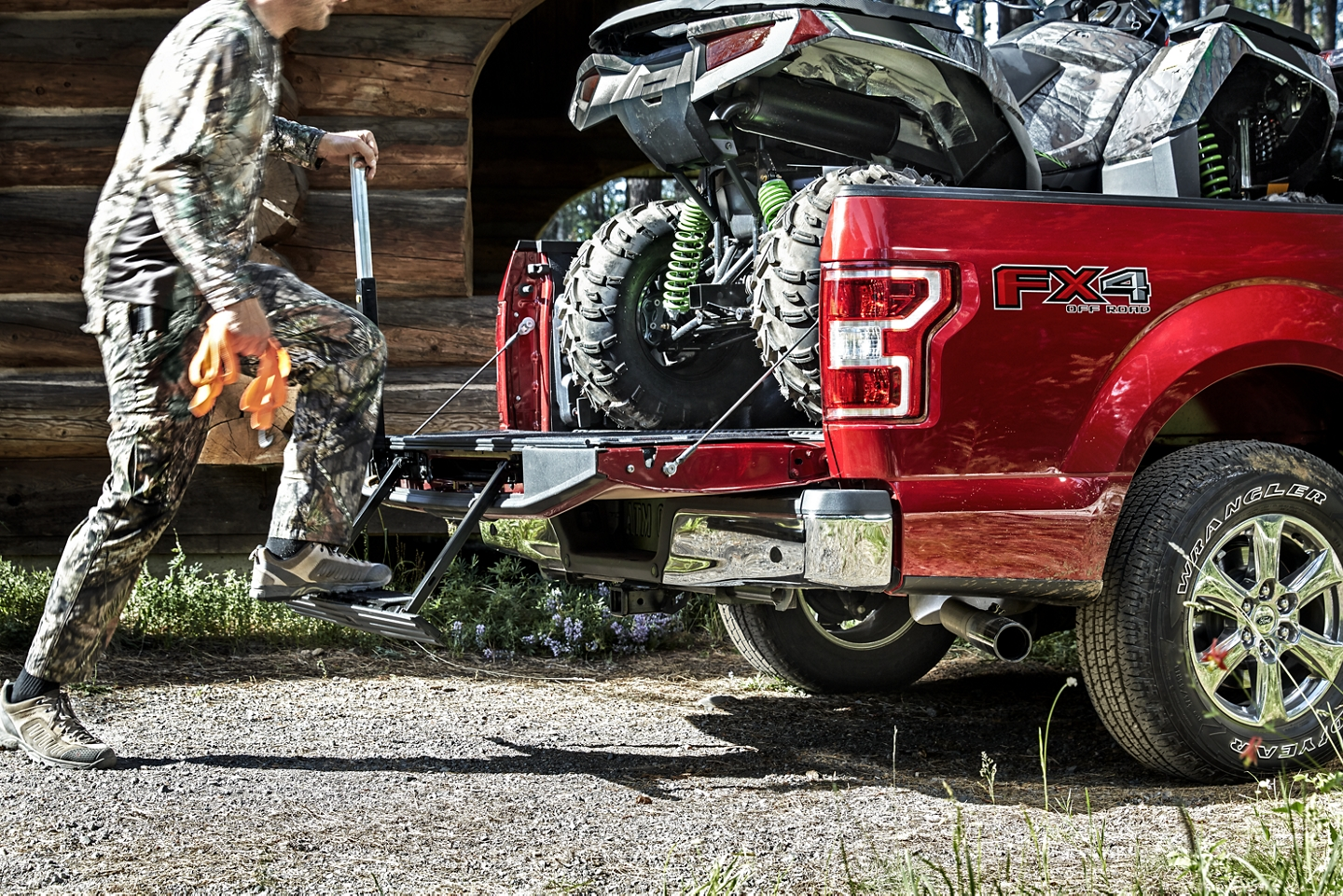 A red 2020 Ford F-150 shows off its customized tailgate while loading a 4-wheeler.