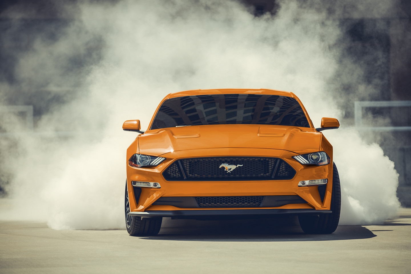 orange 2020 ford mustang doing a burnout