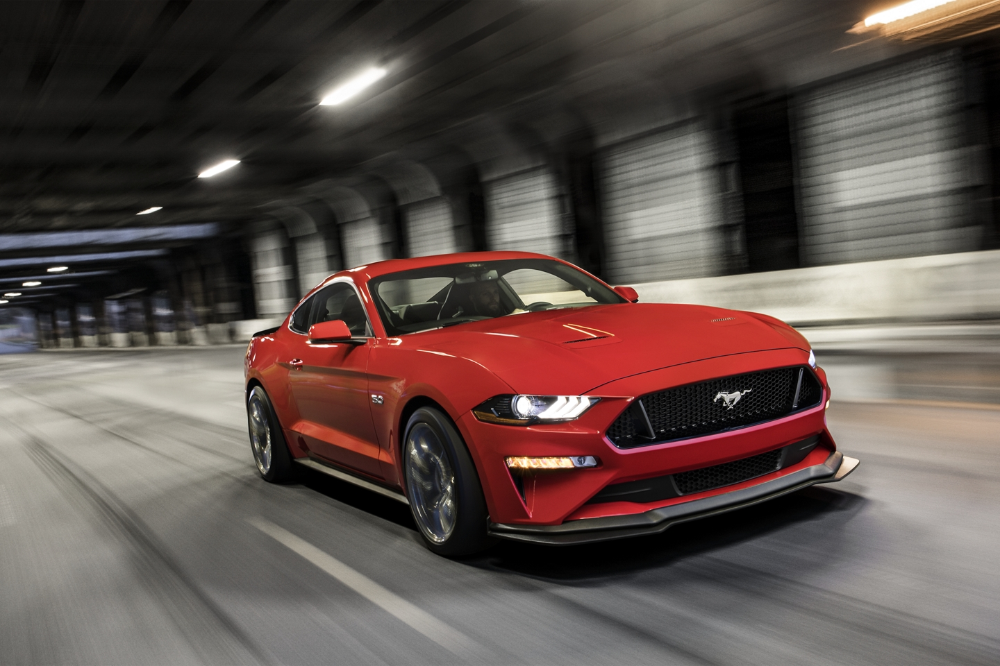 red 2020 ford mustang driving through a tunnel