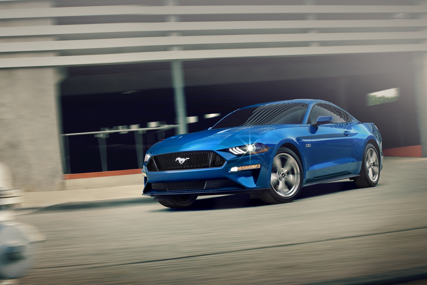 blue 2020 ford mustang turning out of a parking garage