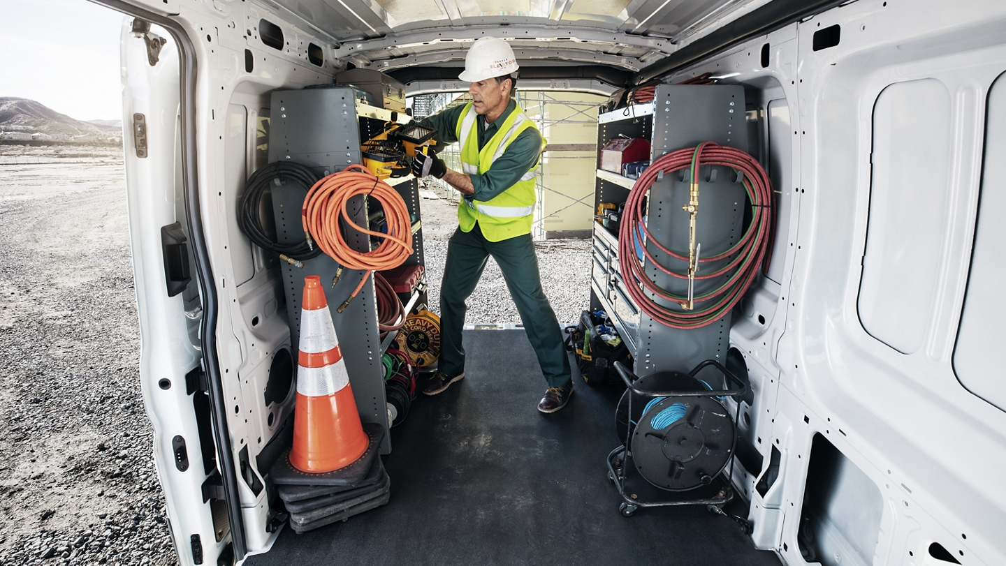 construction worker grabbing gear from the back of a white 2020 ford transit